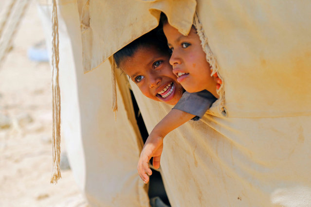 Children look out of their family's tent at a camp for internally displaced people (IDPs) in Marib, Yemen on October 1, 2020. (Photo by Nusaibah Almuaalemi/Reuters)
