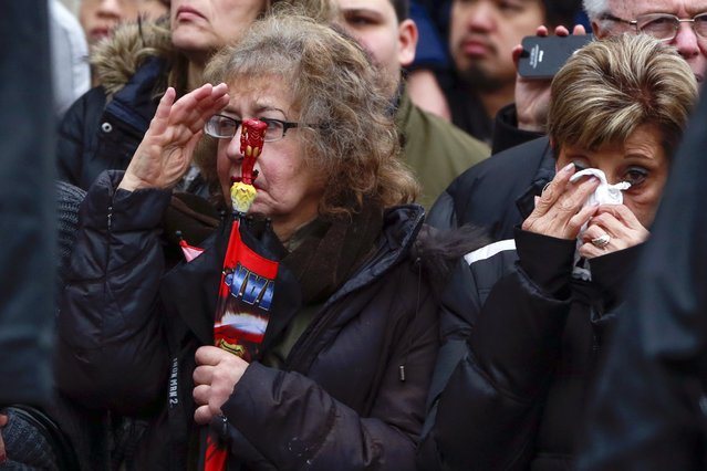 A woman salutes as another wipes tears from her eyes along the funeral procession route for NYPD officer Wenjian Liu in the Brooklyn borough of New York January 4, 2015. (Photo by Shannon Stapleton/Reuters)