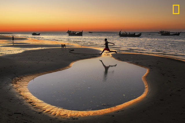 """""""A boy crossing the little pond beside sea beach at Coxís Bazar Dry fishing village, Bangladesh. In the village more than 5000 families engaged with dry fish processing. Their children have no modern toys to paly, so some times they play and making fun by themselves like as jumping or running"""". (Photo by Yousuf Tushar/National Geographic Travel Photographer of the Year Contest)"""