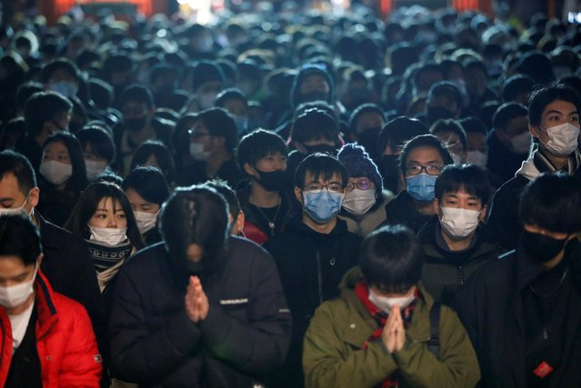 People wearing protective face masks gather as they offer prayers on the first day of the New Year at the Kanda Myojin shrine in Tokyo, Japan, January 1, 2021. (Photo by Issei Kato/Reuters)