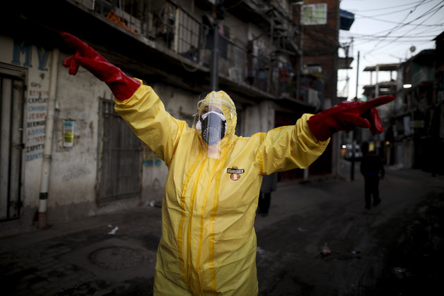 In this Monday, May 18, 2020 file photo, Jimena Aballe directs her neighbors as they disinfect their own streets in the Villa 31 neighborhood to curb the spread of COVID-19 in Buenos Aires. Winter is ending in the Southern Hemisphere and country after country – South Africa, Australia, Argentina – had a surprise: Their steps against COVID-19 also apparently blocked the usual flu epidemic. (Photo by Natacha Pisarenko/AP Photo)