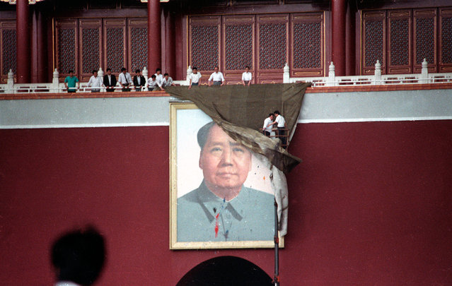 Workmen try to drape the portrait of Mao Tse-tung in Beijing's Tiananmen Square after it was pelted with paint, on May 23, 1989. (Photo by Ed Nachtrieb/Reuters)