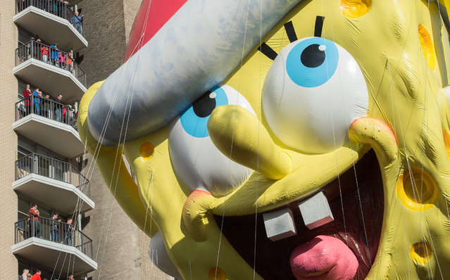 Spectators watch as the balloon of Spongebob Squarepants is moved down Central Park West during the Macy's Thanksgiving Day Parade, Thursday, November 26, 2015, in New York. (Photo by Bryan R. Smith/AP Photo)