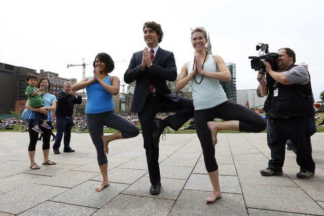 Liberal leader Justin Trudeau (C) poses with yoga enthusiasts following a news conference on Parliament Hill in Ottawa June 5, 2013. (Photo by Chris Wattie/Reuters)