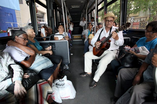 Jorge Luis Jimenez (2nd R) plays the guitar for passengers on a public bus in San Juan, December 2, 2015. Puerto Rico made a crucial debt payment on Tuesday but warned that its deteriorating finances could trigger future defaults, as the governor granted the U.S. territory power to take revenues from public agencies. (Photo by Alvin Baez/Reuters)