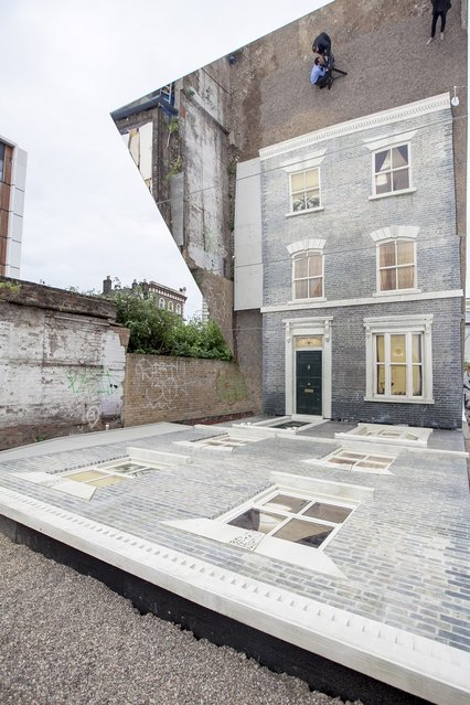 "A large-scale installation art piece by Leandro Erlich, named ""Dalston House"", is displayed on June 24, 2013 in London, England. Part of the ""Beyond Barbican"" summer series of events, the interactive installation is a full facade of a late nineteenth-century Victorian terraced house built on the ground with a large mirror above it to reflect people as to appear dangling from the structure.  (Photo by Dan Dennison/Getty Images)"