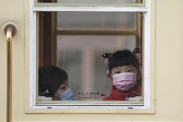 A child and a woman, both wearing face masks to help curb the spread of the coronavirus, ride a train at Qianmen Street, a popular tourist spot in Beijing, Sunday, January 31, 2021. A World Health Organization team looking into the origins of the coronavirus pandemic on Sunday visited the seafood market in the Chinese city of Wuhan that was linked to many early infections. (Photo by Andy WongAP Photo)