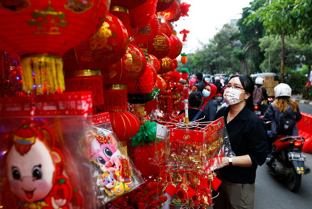 A woman wearing a protective mask shops at a street market selling decorations ahead of the Lunar New Year, following the coronavirus disease (COVID-19) outbreak, in Jakarta, Indonesia, February 4, 2021. (Photo by Ajeng Dinar Ulfiana/Reuters)