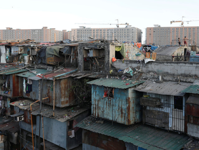 Residents stand on a rooftop of a shanty tenement house while newly-built condominium buildings are seen in the background in Tondo district, metro Manila, Philippines, March 11, 2018. (Photo by Dondi Tawatao/Reuters)