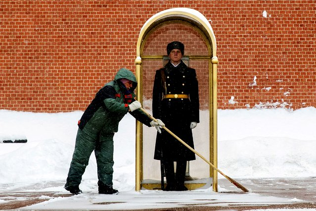 A municipal worker clears snow as an honor guard soldier stands in his station at the Tomb of Unknown Soldier in Moscow, Russia, Friday, February 12, 2021. The weekly temperature in Moscow is around –12 degree Celsius ( 10.4 degree Fahrenheit) during the day and drops to –18 at night ( –0.4 degree Fahrenheit). (Photo by Pavel Golovkin/AP Photo)