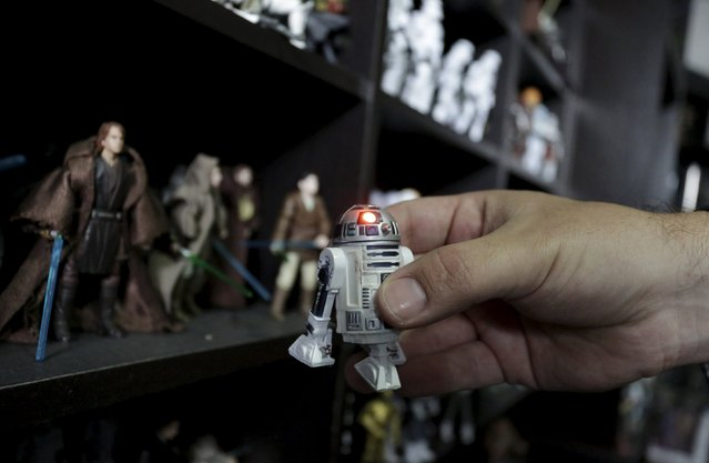 Mexican collector Pablo Perez, holds up a Star Wars R2-D2 toy while he displays a toy collection of Star Wars characters and items at his home in Monterrey, Mexico December 12, 2015. (Photo by Daniel Becerril/Reuters)