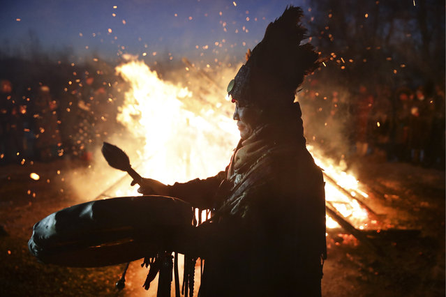 A shaman conducts San Salyr, a sacred fire lighting rite, during celebrations of Shagaa, the Lunar New Year, in National Park in Tyva Republic, Russia on February 12, 2021. Lunar New Year 2021 is the Year of the Ox. (Photo by Kirill Kukhmar/TASS)