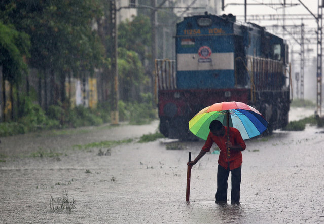 A gangman attempts to unclog a gutter at a railway track during heavy rains in Mumbai, July 9, 2018. (Photo by Francis Mascarenhas/Reuters)