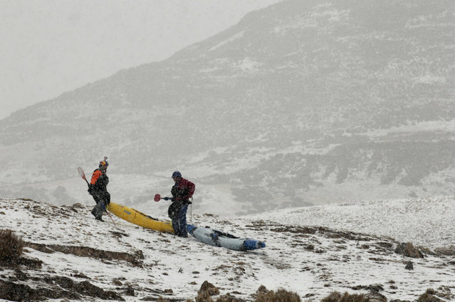 August 18, 2012 – Alpamarca, Peru – Amazon Express white water team member Rafael Ortiz, of Mexico, and expedition leader West Hansen, of Austin, Texas, portage their kayaks through a snow storm shortly after the start of white water kayaking out of Lago Acucocha. (Photo by Erich Schlegel/zReportage via ZUMA Press)