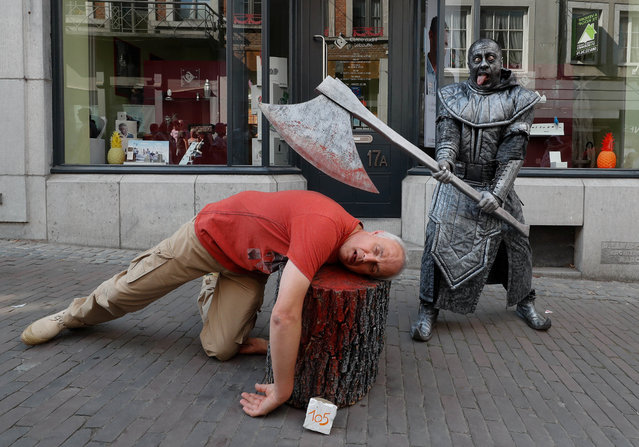 "An artist called ""Le Bourreau/The Headsman"" takes part in the festival ""Statues en Marche"" in Marche-en-Famenne, Belgium, July 22, 2018. A man and a woman made entirely of chocolate, a mermaid with a flowing tail and an axe-wielding medieval executioner were also on display at the annual event in Marche-en-Famenne. (Photo by Yves Herman/Reuters)"