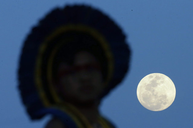A Brazilian indigenous person walks under a full moon as he attends the World Indigenous Games in Palmas, Brazil, 26 October 2015. The multisport event, with over 2,000 participating indigenous athletes from 30 countries from all over world, runs until 01 November. (Photo by Fernando Bizerra Jr./EPA)
