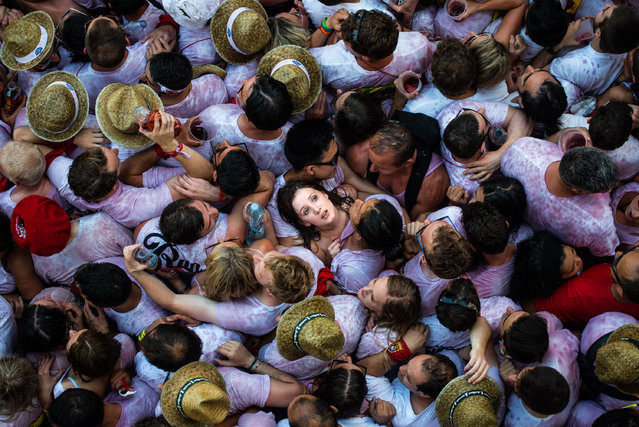 """Revellers enjoy the atmosphere during the opening day or """"Chupinazo"""" of the San Fermin Running of the Bulls fiesta on July 6, 2015 in Pamplona, Spain. The annual Fiesta de San Fermin, made famous by the 1926 novel of US writer Ernest Hemmingway entitled """"The Sun Also Rises"""", involves the daily running of the bulls through the historic heart of Pamplona to the bull ring. (Photo by David Ramos/Getty Images)"""