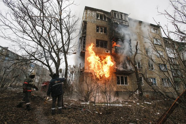 A firefighter (L) walks to the front of a residential block that has been set on fire, caused by a recent shelling according to locals, as his colleagues arrive to extinguish the fire on the outskirts of Donetsk, eastern Ukraine February 9, 2015. (Photo by Maxim Shemetov/Reuters)