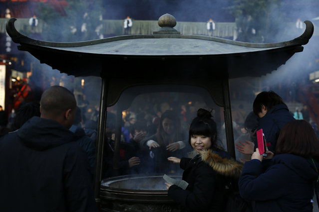 A woman has her picture taken at a incense burner outside the Sensoji temple ahead of the New Year holidays in Tokyo, Japan December 30, 2015. (Photo by Thomas Peter/Reuters)