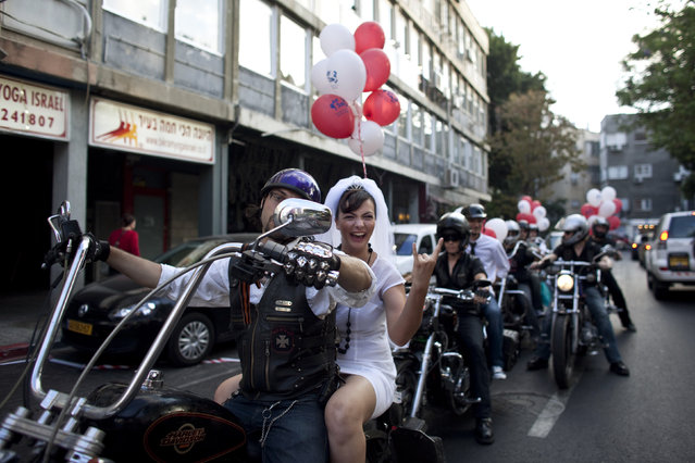 Bride Yulia Tagil sits on the backseat of a bike as she arrives for her alternative wedding ceremony on a square in Tel Aviv July 25, 2010. The alternative wedding ceremony was intended to demonstrate against the current situation in Israel, where the only way for Jews to get married by law is through the Chief Rabbinate. (Photo by Nir Elias/Reuters)