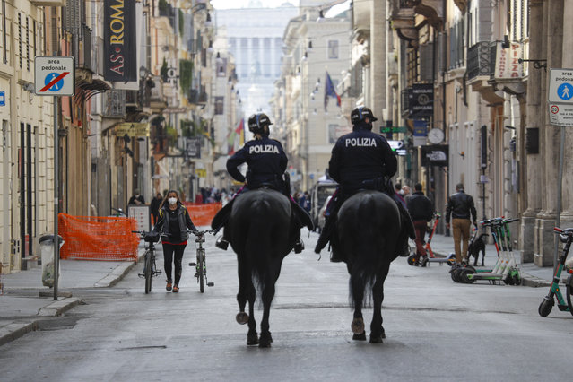 Mounted police officers patrol Via del Corso main shopping street, in downtown Rome, Saturday, April 3, 2021. Italy went into lockdown on Easter weekend in its effort to battle then Covid-19 pandemic. (Photo by Gregorio Borgia/AP Photo)