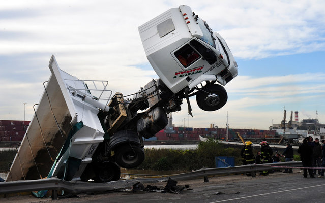 A lorry carrying sand slided off the road for undetermined reasons and fell into the the river at the waterfront in Buenos Aires, on August 12, 2013 but without causing casualties whatsoever. (Photo by Daniel Garcia/AFP Photo)