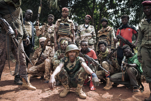 Militiamen, including alleged children, of the armed group coalition Coalition of Patriots for Change (CPC) pose for a photograph in the village of Niakari, which marks the front line with the Central African army and its allies, north of Bangassou, on January 30, 2021. On January 3, 2021, the city of Bangassou was attacked by hundreds of CPC militiamen, causing tens of thousands of people to flee into the bush and neighboring DR Congo. Since the end of December 2020, the rebel coalition has taken control of the main roads and several of the country's major cities. (Photo by Alexis Huguet/AFP Photo)