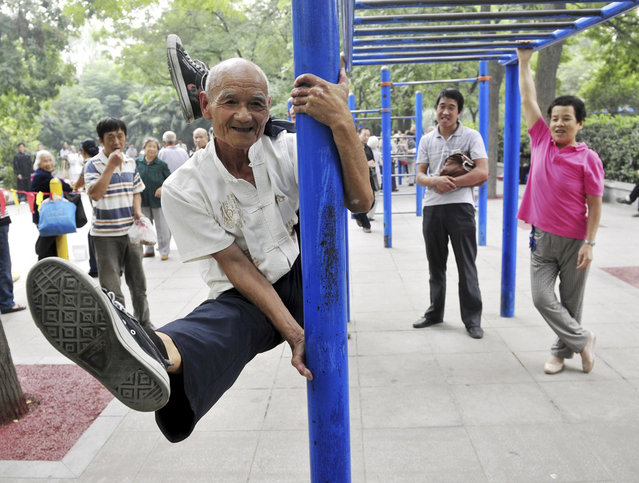 Yang Shiguang, 77, performs stunts at a park in Xi'an, Shaanxi province, September 3, 2013. Yang has been a member of a stunt performance club since 2007, after retiring from a research institution. (Photo by Reuters/China Daily)
