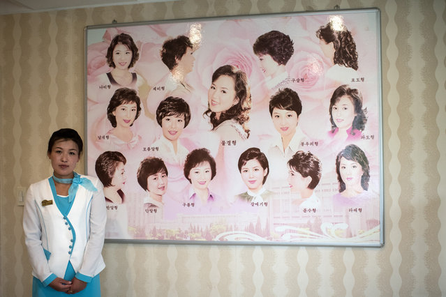 A member of staff pauses next to a board displaying approved hairstyles at a women's salon in the Munsu Water Park complex on August 19, 2018 in Pyongyang, North Korea. (Photo by Carl Court/Getty Images)