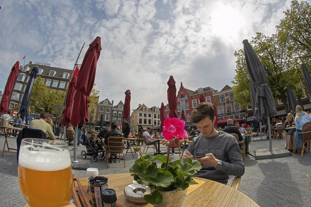 A guest shows his glass of beer to the photographer as Dutch customers eager for their first drink of coffee or something stronger at a cafe terrace have flocked to outdoor seating as the Netherlands' lockdown eased in Utrecht, Wednesday, April 28, 2021. The Netherlands became the latest European country to begin cautiously relaxing its lockdown even as infection rates and intensive care occupancy remain stubbornly high. The Dutch follow Italy, Greece, France and other European nations in moving to reopen society and edge away from economically crippling lockdowns in the coming weeks.(Photo by Peter Dejong/AP Photo)