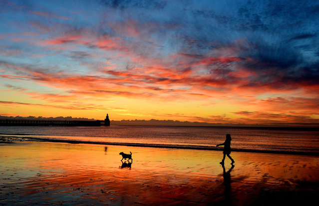 A woman walks her dog at sunrise on Blyth beach, Northumberland, September 18, 2013. (Photo by Owen Humphreys/PA Wire)