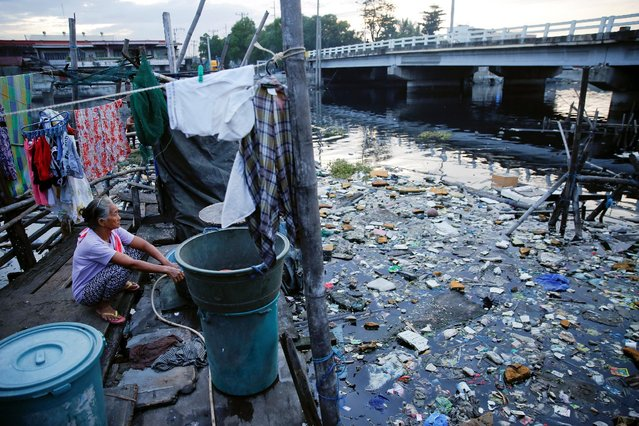 A woman washes clothes at a local community living near the C-3 bridge in North Bay Boulevard South (NBBS), a Navotas City district of slums and waterways with a high number of drug war deaths, in Manila, Philippines November 3, 2016. (Photo by Damir Sagolj/Reuters)