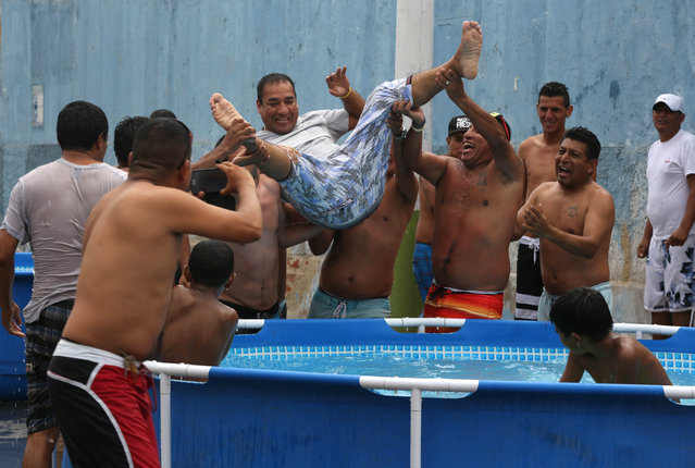 A group of friends lift Juan Carlos Durand, to toss him in to a plastic pool filled with water, in Callao, Peru, Sunday, February 22, 2015. Temperatures in Callao can top 30 degrees Celsius (86 Fahrenheit) in February, which is also the month of Peru's water carnival when people celebrate with water fights and hurling water balloons. (Photo by Martin Mejia/AP Photo)