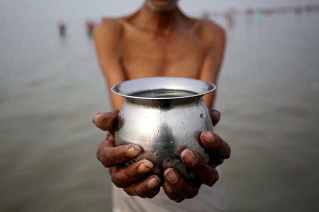 An Indian devotee prays as he takes a holy bath in the Bay of Bengal during the Gangasagar Fair at Sagar Island, eastern India, Thursday January 14, 2016. The event is an annual gathering of Hindu pilgrims during Makar Sankranti at Sagar Island, 130 km south of Calcutta in West Bengal, to take a dip in sacred waters of Ganga River before she merges in the Bay of Bengal.  (Photo by Piyal Adhikary/EPA)