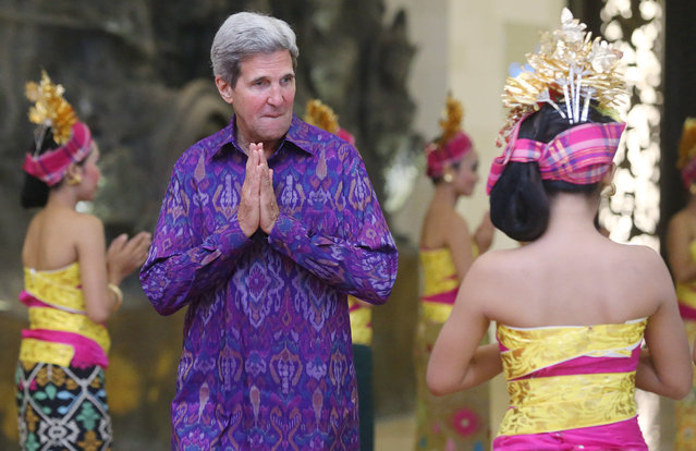 US Secretary of State John Kerry, welcomed by Indonesian beauties, gestures while arriving with Russian President Vladimir Putin (L) for a group photo at Asia-Pacific Economic Cooperation (APEC) Summit  in Nusa Dua, Bali, Indonesia, 7 October 2013. (Photo by Sergei Chirikov/EPA)
