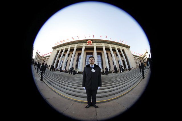 Security guards stands outside the Great Hall of the People ahead of the opening session of Chinese People's Political Consultative Conference (CPPCC) at Tiananmen Square in Beijing, March 3, 2015. Picture taken with fisheye lens. REUTERS/Kim Kyung-Hoon