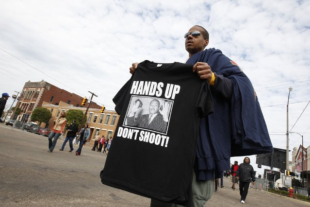 "A man hawks his t-shirts which say ""Hands Up Don't Shoot"" before the 50th anniversary of the Selma to Montgomery civil rights march in Selma, Alabama March 8, 2015. REUTERS/Tami Chappell  (UNITED STATES - Tags: POLITICS ANNIVERSARY SOCIETY)"