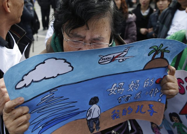 "Wang Guohui, mother of Li Zhi, a passenger of the missing Malaysia Airlines flight MH370, cries while holding a painting which her family made for wishing the return of her son during a gathering of family members of the missing passengers at Yonghegong Lama Temple in Beijing March 8, 2015. Prime Minister Najib Razak said on Sunday Malaysia remains committed to the search for the missing MH370 jetliner a year after it vanished without trace and he is hopeful it will be found. The message on the painting reads, ""Mother's heart is broken, where are you, my son."" REUTERS/Kim Kyung-Hoon (CHINA - Tags: TRANSPORT DISASTER)"