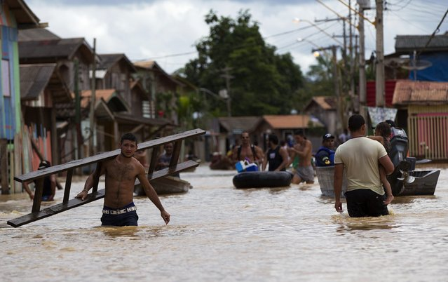 Residents wade through a neighbourhood flooded by the Purus river, which continues to rise from days of heavy rainfall in the region, in Boca do Acre, Amazonas state March 14, 2015. (Photo by Bruno Kelly/Reuters)