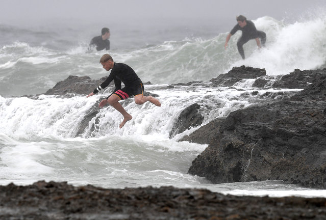 A surfer (C) jumps from the rocks into the surf at Snapper Rocks on the Gold Coast, Australia, 05 April 2021. The Bureau of Meteorology has cancelled a severe weather warning as a low weather system remains off the coast of Fraser Island, gale-force wind warnings remain in place for waters off the Sunshine Coast and Gold Coast. (Photo by Darren England/EPA/EFE)