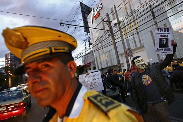 """A demonstrator wearing a Guy Fawkes mask (R) holds a sign during a protest against the dismissal of two investigative journalists Daniel Lizarraga and Irving Huerta from a news programme on MVS Radio, outside the station in Mexico City March 12, 2015. Lizarraga and Huerta were fired for """"breach of trust"""", the station said in a statement Thursday morning. The sign, referring to Carmen Aristegui, anchor of the radio news programme. (Photo by Edgard Garrido/Reuters)"""