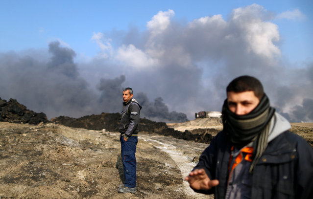 Men stand in front of oilfields burned by Islamic State fighters in Qayyara, south of Mosul,Iraq.December,21, 2016. (Photo by Ammar Awad/Reuters)