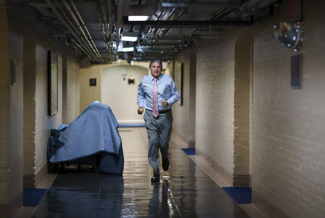 Sen. Joe Manchin, D-W.Va., one of the key Senate infrastructure negotiators, rushes back to a basement room at the Capitol as he and other Democrats work behind closed doors, in Washington, Wednesday, June 16, 2021. (Photo by J. Scott Applewhite/AP Photo)