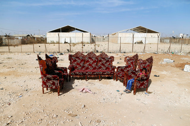 JORDAN: A Syrian refugee girl sits on an armchair for sale at Al-Zaatari refugee camp near the border with Syria, in Mafraq, Jordan October 15, 2016. (Photo by Ammar Awad/Reuters)