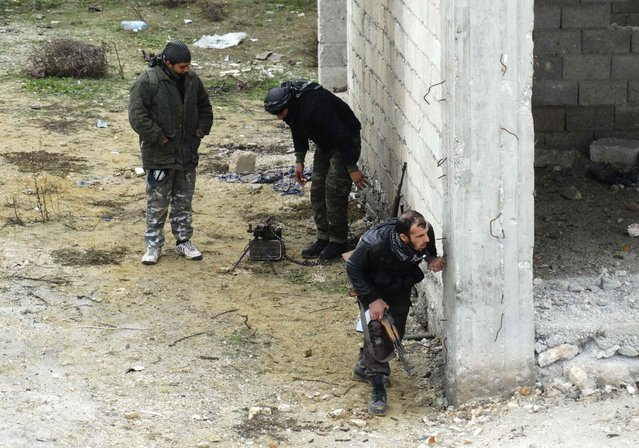 Rebel fighters take positions as one of them peers out from behind a wall at al-Breij frontline, after what they said was an advance by them in al-Manasher and al-Majbal areas where forces loyal to Syria's President Bashar al-Assad were stationed, in Aleppo January 5, 2015. (Photo by Abdalghne Karoof/Reuters)