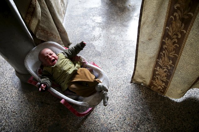 Khouloud, Shahrour's 6-month-old granddaughter, is seen crying in the courtyard of her grandfather's home in the besieged town of Arbeen, in the Damascus suburbs, Syria February 6, 2016. (Photo by Bassam Khabieh/Reuters)