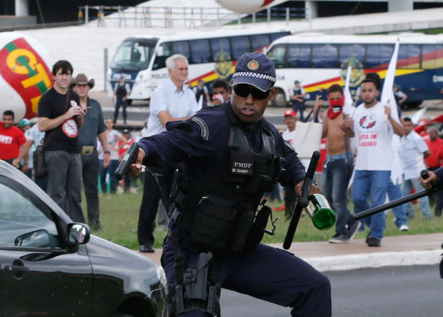 A military police officer aims his gun to a demonstrator during a protest in Brasilia, Brazil, Tuesday, April 7, 2015. The officer had picked up a bottle that was thrown towards them but did not fire his gun and backed away. Thousands of workers have staged rallies in 12 cities across Brazil to protest against a proposed law that would allow companies to outsource their labor force. (Photo by Eraldo Peres/AP Photo)