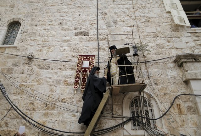 A Greek Orthodox priest is given a book as he stands on a platform during the washing of the feet ceremony outside the Church of the Holy Sepulchre in Jerusalem's Old City, April 9, 2015, ahead of Orthodox Easter. (Photo by Ammar Awad/Reuters)