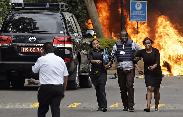Security forces help civilians flee the scene as cars burn behind, at a hotel complex in Nairobi, Kenya Tuesday, January 15, 2019. Terrorists attacked an upscale hotel complex in Kenya's capital Tuesday, sending people fleeing in panic as explosions and heavy gunfire reverberated through the neighborhood. (Photo by Ben Curtis/AP Photo)