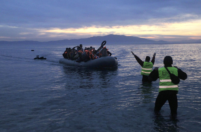 Volunteers of an NGO direct refugees and migrants arriving in a dinghy from Turkey to the coast of Mytilini, on the island of Lesvos, Greece, 17 February 2016. Around 1 million people, including many refugees from war zones in the Middle East and Central Asia, passed through Greece and along the Balkan route in 2015, most of them in the latter half of the year. (Photo by Orestis Panagiotou/EPA)